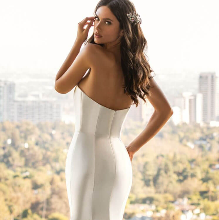 Model wearing a backless white gown